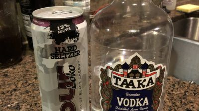 a bottle of cheap vodka and a tall boy can of four loko hard seltzer