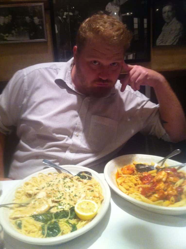 jason doing a sexy pose with two plates of pasta in front of him