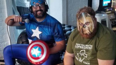 dave b dressed as captain america sitting next to Jason wearing a paper chewbacca mask
