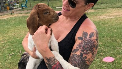 deb on a farm holding a goat in her arms