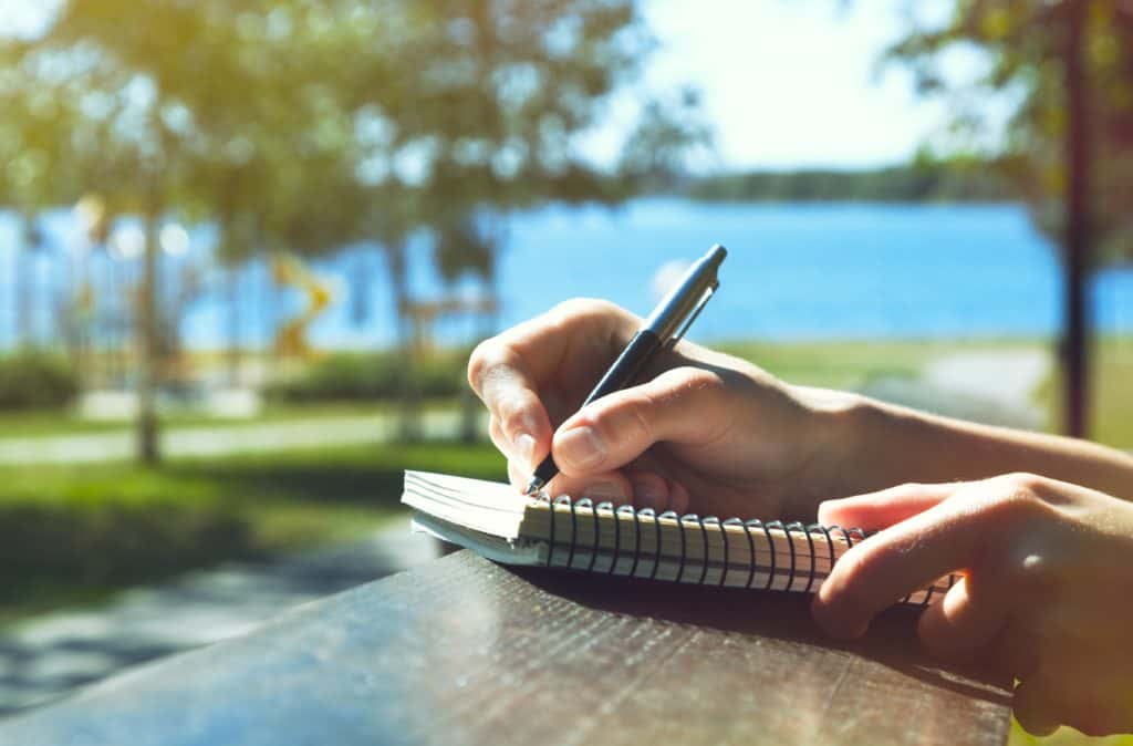 a stock photo of someone writing in a diary outside