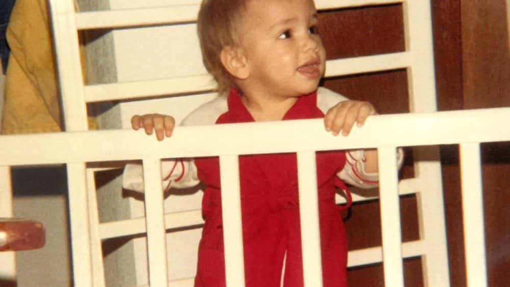 baby nick standing in a crib