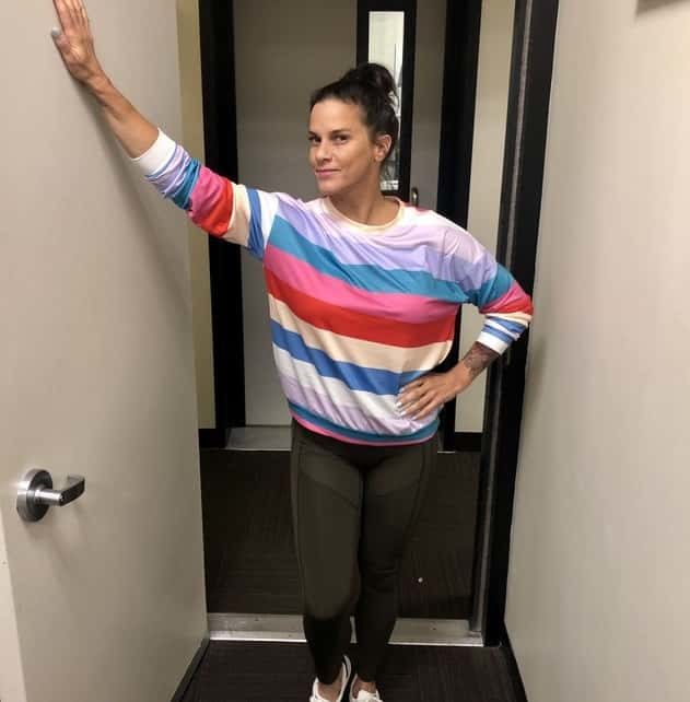 Deb in the studio hallway wearing her multicolored shirt from instagram