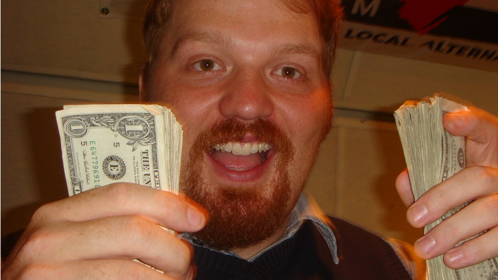 jason holding stacks of money in each hand with a bleep eating grin on his face