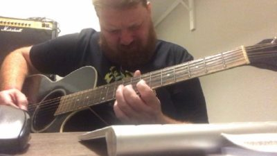 jason playing the guitar in his home office slash closet