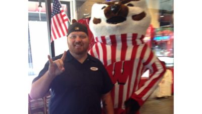 jason doing the hookem horns next to bucky the badger