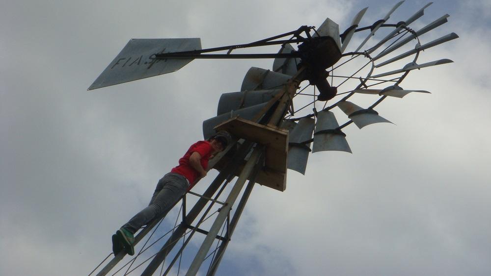 Deb climbing a windmill to fix it
