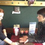 Deb getting a psychic reading from a palm reader