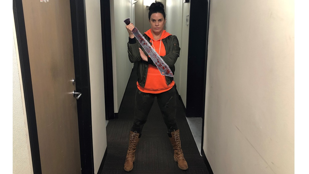 deb wearing her zombie apocalypse outfit consisting of a bright orange hoodie, camo leggings, and boots that go up to her knees
