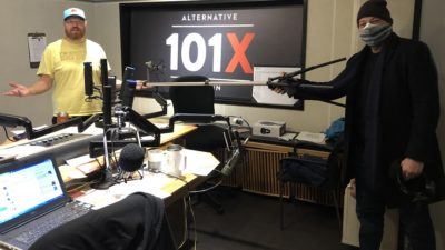 Andy langer in studio holding up a six foot poll between him and Jason