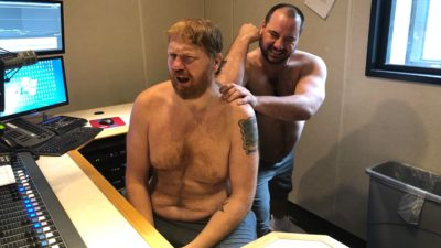 a shirtless nick giving a shirtless jason a back massage in the studio