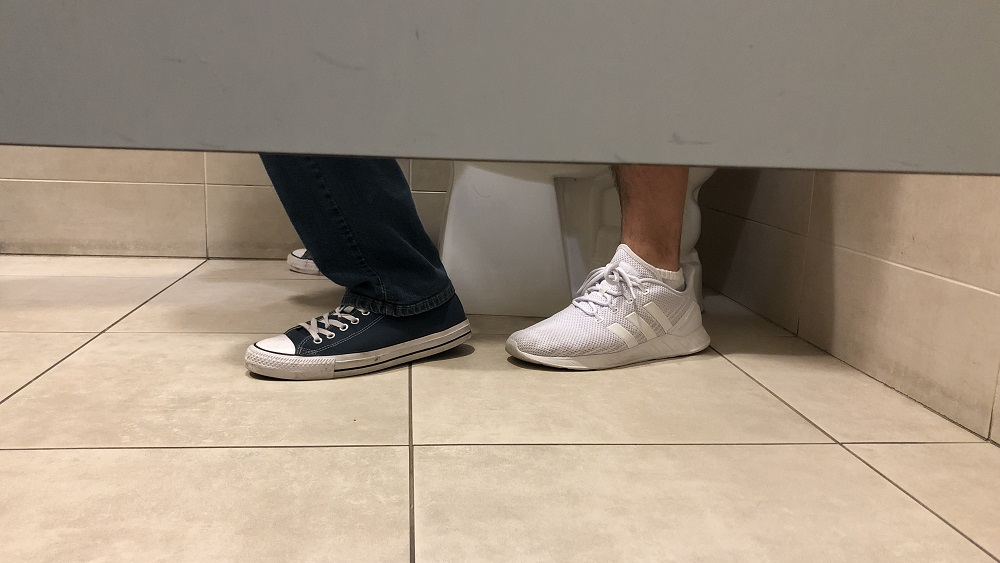 view of a toilet stall showing two pair of feet implying two people are on the toilet at the same time