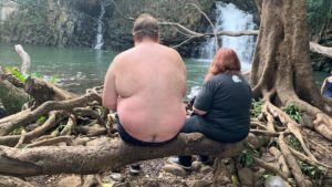 Jason and his mom sitting on a log at a hawaii watering hole