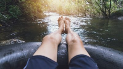 stock photo of a guy tubing the river