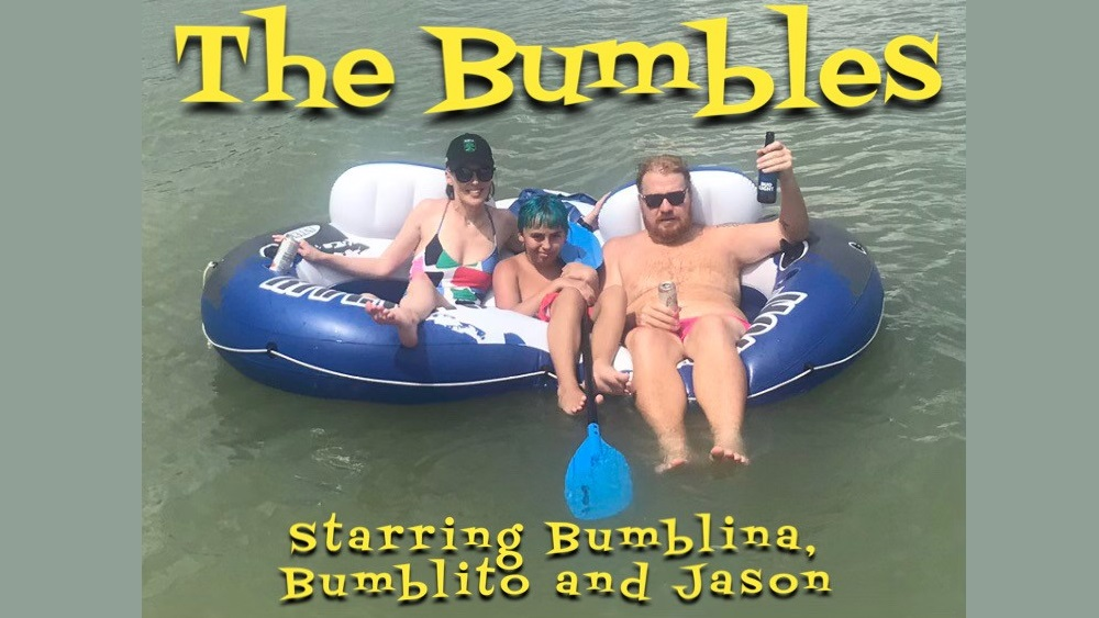 """Jason and his girlfriend and her son floating on the lake, with """"The Bumbles"""" photoshopped onto it"""