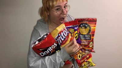 emily holding a bunch of bags of various brands of hot chips