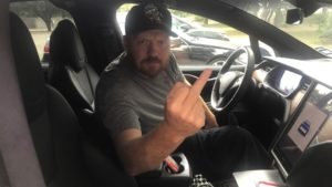 jason flipping the bird from the drivers seat of his tesla