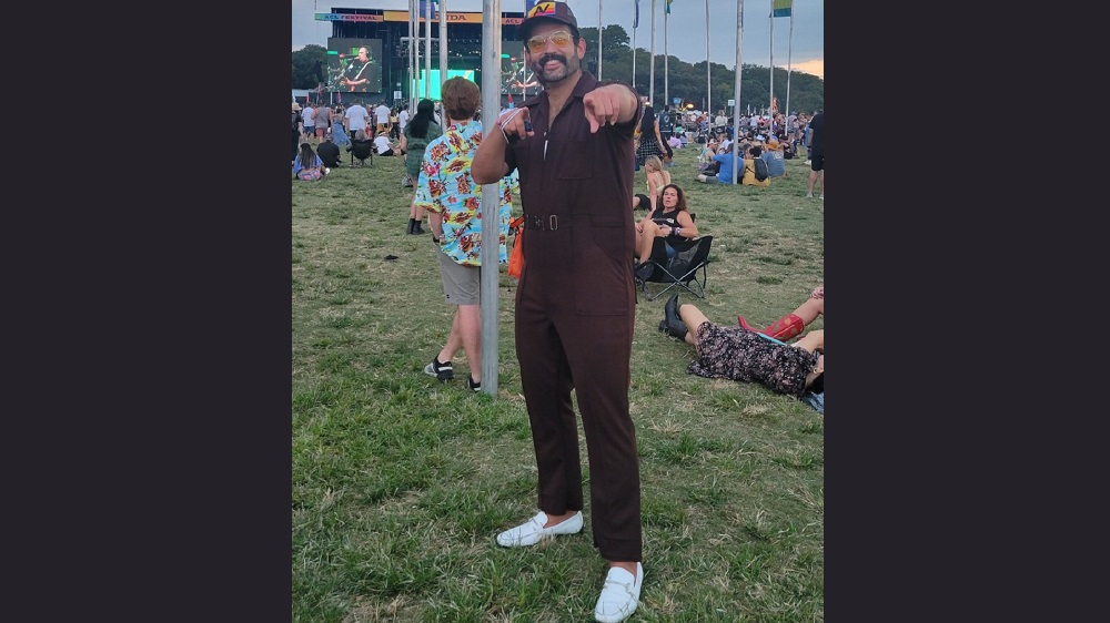 dave b posing in front of acl flags wearing brown ups style onesie