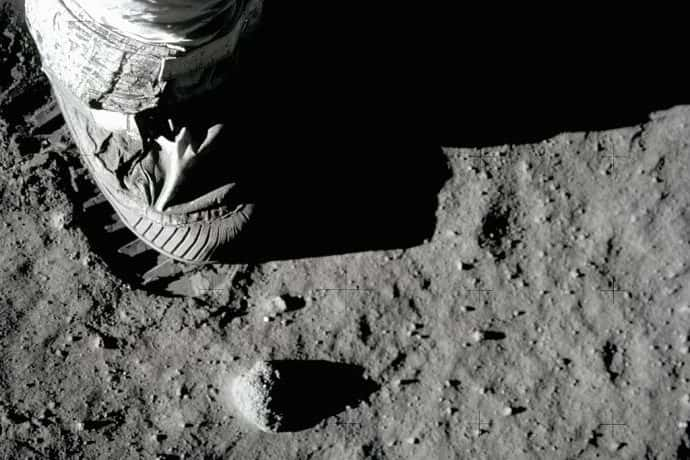 An astronaut wearing a space suit and moon boot steps on the moon's powder gray surface.