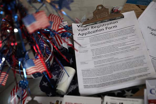 A voter registration form on a clipboard next to several American flags.