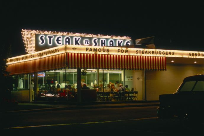A classic Steak n' Shake building is shown with lighted signage. Steak N' Shake is on the verge of bankruptcy.
