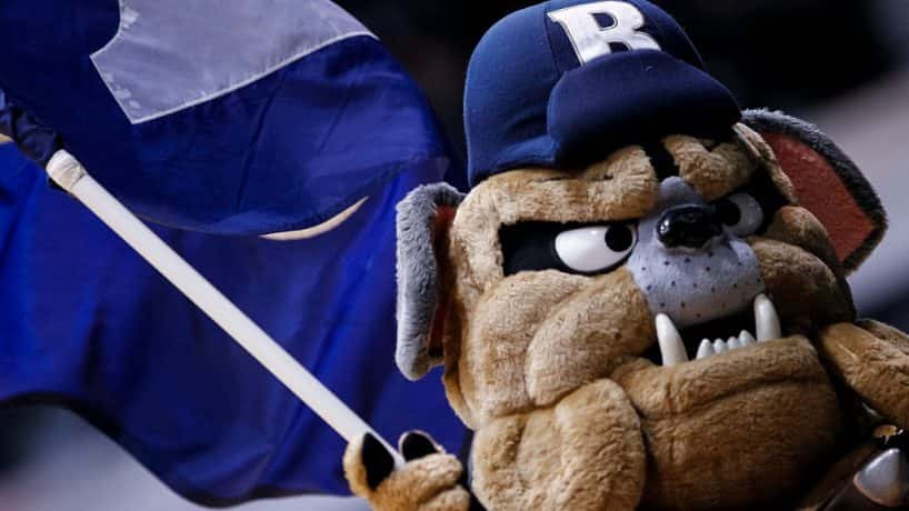 The Butler Bulldog mascot running onto the court holding a Butler flag.