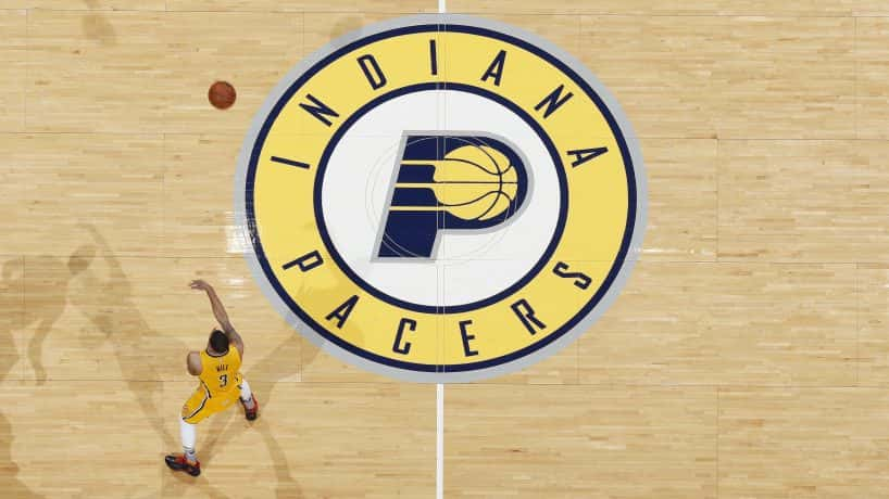 The Pacers logo on a basket ball court with a player running around. (Photo by Joe Robbins/Getty Images)