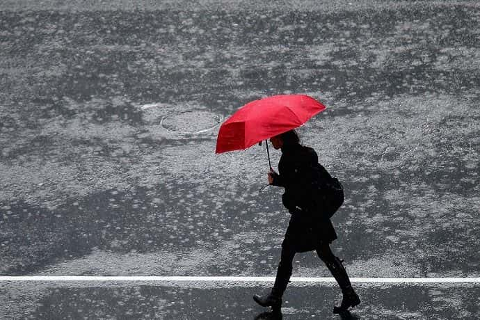 Woman walking down a street in the rain with a red umbrella.