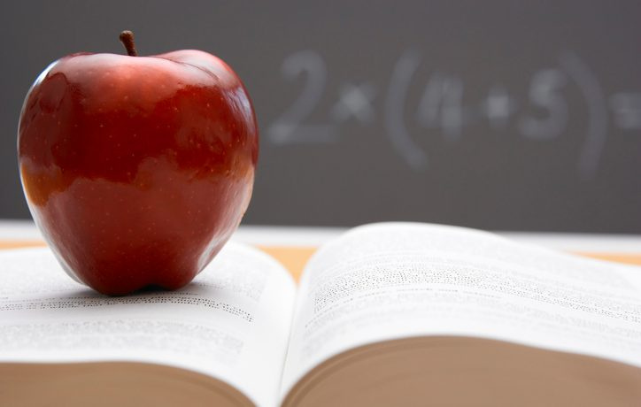 A red apple on top of an open book with a blackboard in the background. Photo by bananastock/Thinkstock.