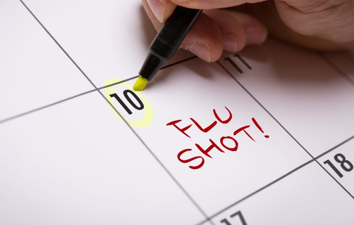 "A person circling the number 10 on a calendar with a highlighter. On the calendar it says, ""Flu shot!"""