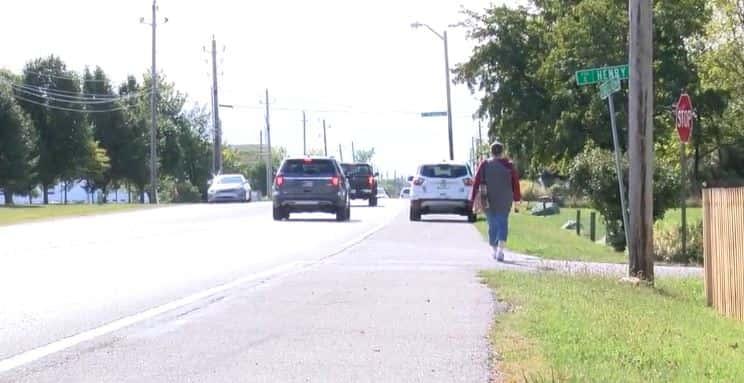 A person walking alongside Girls School Road as cars drive by