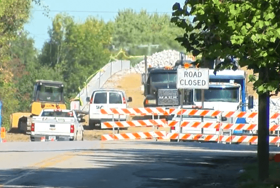"""Road Closed"" signs, construction equipment sit at the Ditch Road bridge over I-465 in Indianapolis."