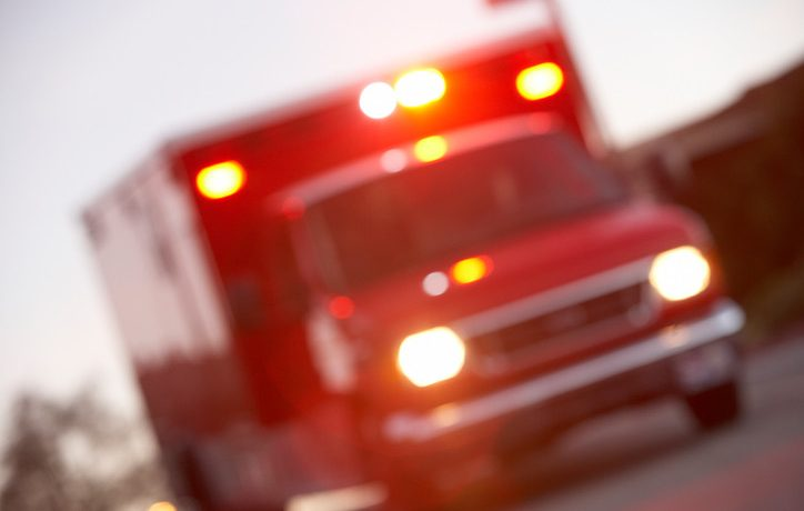 An image of a blurry oncoming ambulance with its sirens and lights on.