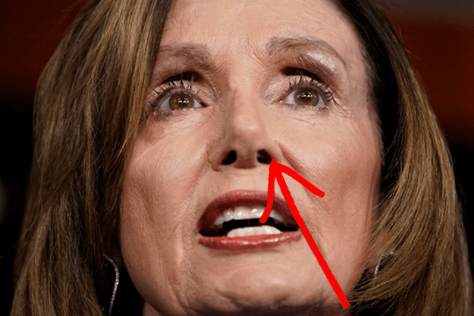 Nancy Pelosi, with hair in nose, addresses media at weekly press conference.