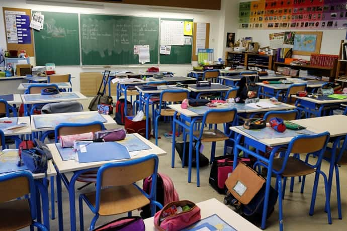 empty classroom with backpacks and pencil pouches (Photo BSIP/UIG/Getty Images)