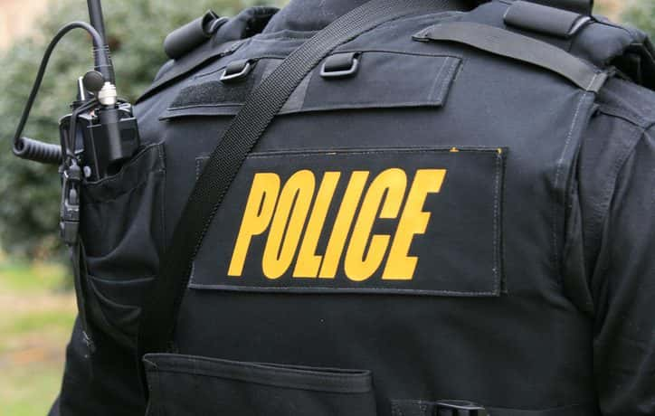 "The rear view of a police officer wearing a bullet-proof vest labeled ""POLICE""."
