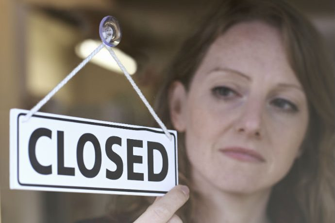 Woman Flipping Sign to Closed