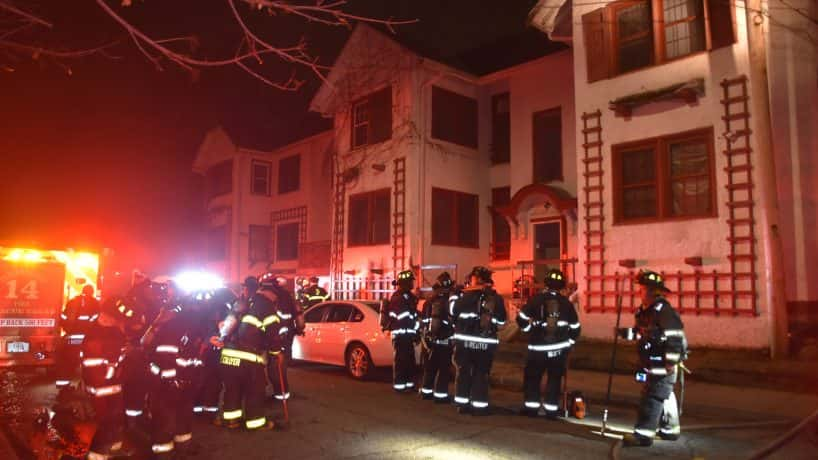 Indianapolis firefighters stand outside an apartment building that caught fire Monday morning.