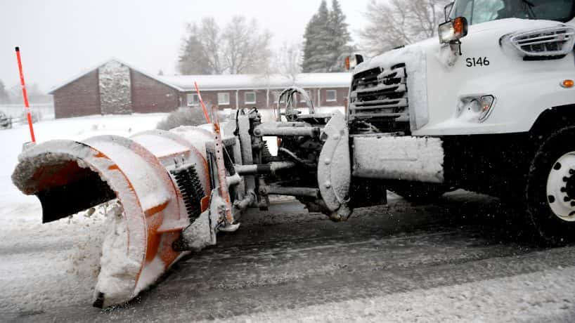 A white truck with a plow, plowing snow on a road.