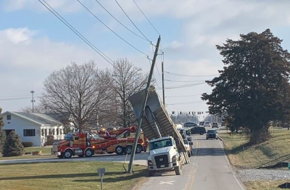 A truck with its bed elevated and touching a utility pole.
