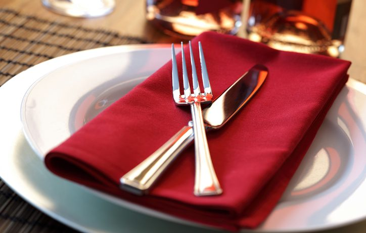 Silverware, a folded napkin, and a plate at a table. Photo by Brian A. Jackson.