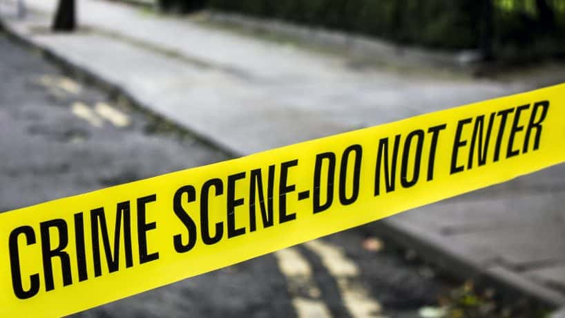 A strip of yellow crime scene tape stretched across a road.