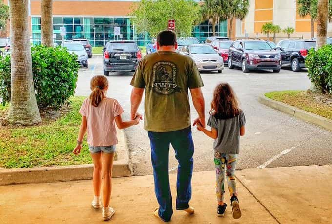Ryan Newman, holding hands with his two daughters, walking out of Helifax Hospital in Daytona Beach, Fla.