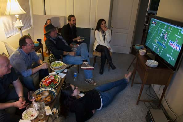 A group of people sitting in a living room, eating, while watching a football game on television