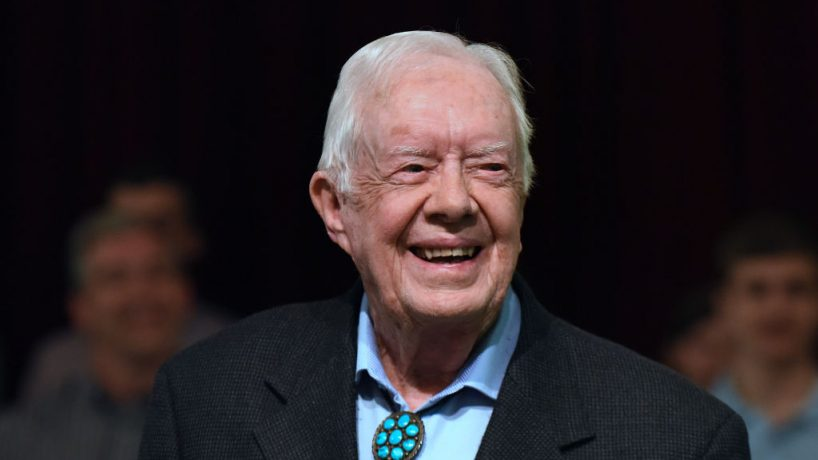 Former Pres. Jimmy Carter smiles in front of crowd.