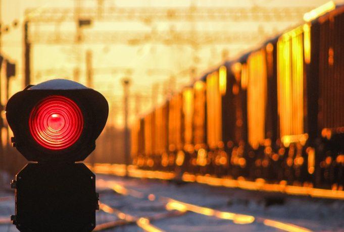 A train going down the tracks next to a flashing red light. Photo by zazamaza/Thinkstock.