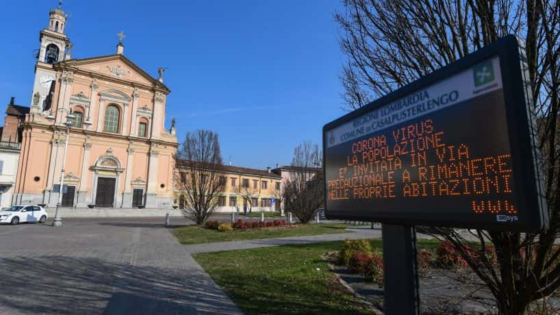 A coronavirus precaution message in Italian outside a building in Italy