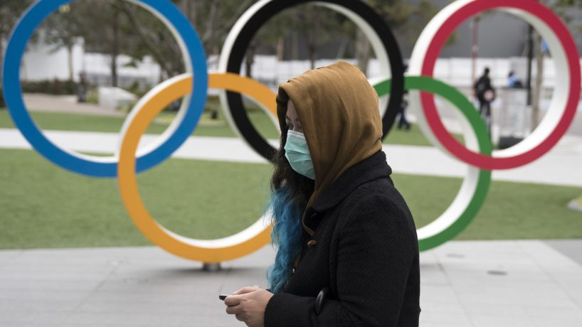 TOKYO, JAPAN - FEBRUARY 26: A woman wearing a face mask walks past the Olympic rings in front of the new National Stadium, the main stadium for the upcoming Tokyo 2020 Olympic and Paralympic Games, on February 26, 2020 in Tokyo, Japan. Concerns that the Tokyo Olympics may be postponed or cancelled are increasing as Japan confirms 862 cases of Coronavirus (COVID-19) and as some professional sporting contests are being called off or rescheduled and some major Japanese corporations ask for people to work from home.