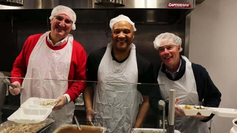 Eric Holcomb, Andre Carson and Joe Hogsett at the Mozell Sanders Thanksgiving dinner.