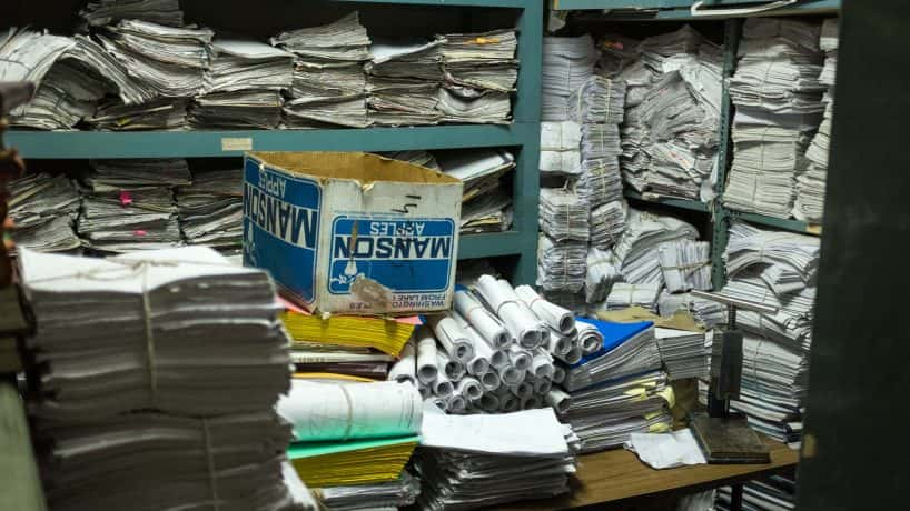 stacks of files and papers in a storage room